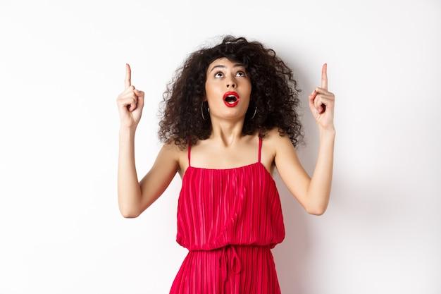 Zdziwiona dziewczyna z wieczorowym makijażem i kręconymi włosami, patrząc i skierowana w górę podekscytowana, pokazująca reklamę, stojąca w czerwonej sukience na białym tle.
