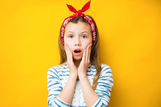 Zdziwiona dziewczynka dziecko na żółtym tle