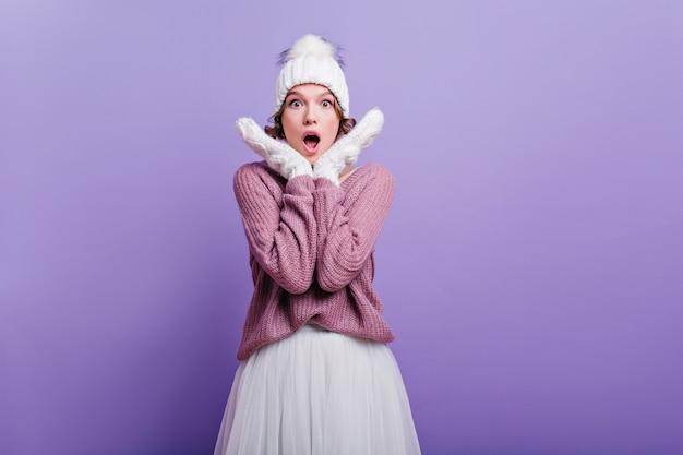Zdziwiona dziewczynka kaukaski w zimowy strój z fioletowym wnętrzem. zaskoczona młoda kobieta w białej spódnicy i sweter z dzianiny stoi z otwartymi ustami.