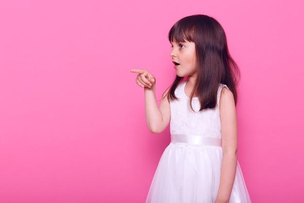 Zdziwiona dziewczynka ubrana w elegancką białą sukienkę, patrzy na przód, wskazując palcem, pokazując szokujące rzeczy, kopiuj przestrzeń, odizolowana na różowej ścianie
