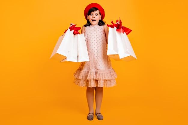 Zdziwiona dziewczynka w berecie francuskim pozuje po zakupach. zdumiony dzieciak z papierowymi torbami.