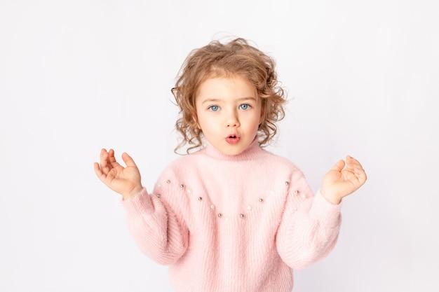 Zdziwiona dziewczynka w różowe zimowe ubrania na białym tle, miejsca na tekst