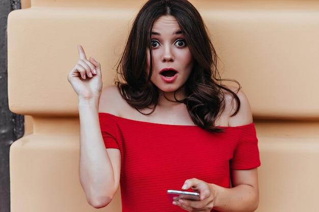 Zdziwiona europejska kobieta z telefonem w ręku, pozowanie przed ścianą. plenerowe ujęcie zdumionej dobrze ubranej kobiety o ciemnych włosach.