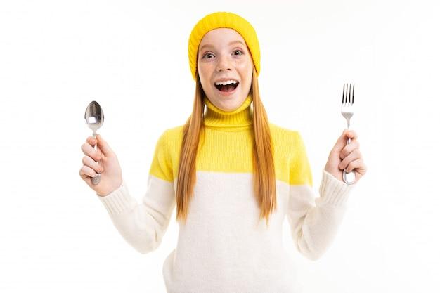 Zdziwiona europejska miedzianowłosa dziewczyna trzyma nóż na bielu i rozwidlenie