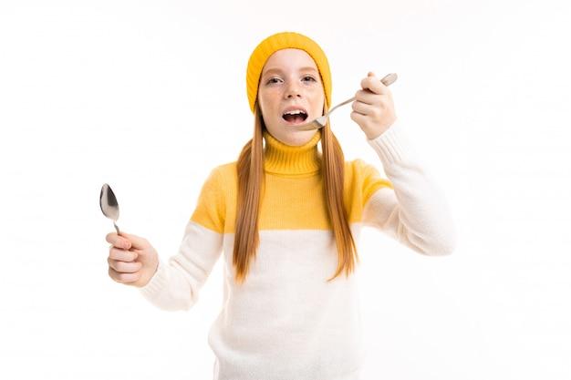 Zdziwiona europejska miedzianowłosa młoda dziewczyna trzyma nóż na bielu i rozwidlenie