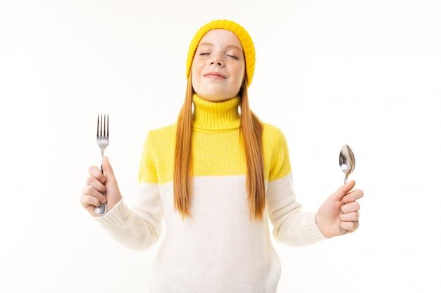 Zdziwiona europejska rudowłosa dziewczyna trzyma nóż i widelec na białej ścianie
