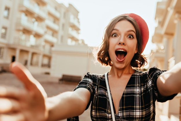 Zdziwiona francuzka o brązowych oczach robi selfie na ulicy. śmieszne kręcone dziewczyna w czerwonym berecie robi sobie zdjęcie podczas spaceru po mieście.