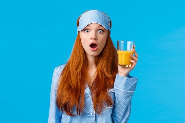 Zdziwiona i niemowa kaukaska lisia kobieta w bieliźnie nocnej, piżamie i masce do spania, z otwartymi ustami, zastanawia się, jak trzyma sok pomarańczowy, ogląda wiadomości poranne śniadanie, niebieska ściana