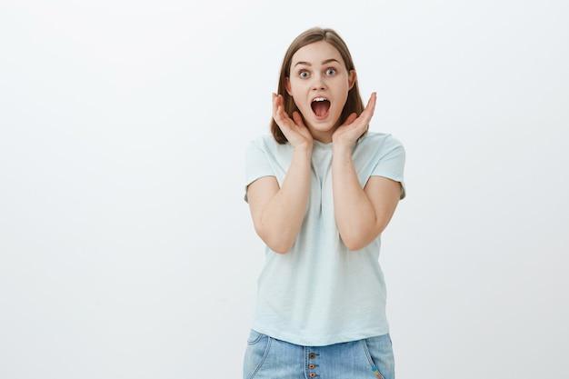 Zdziwiona i rozbawiona dziewczyna nie może uwierzyć własnym uszom. portret zdumionej, zaskoczonej, entuzjastycznej europejki w modnej koszulce, krzyczącej z radości i zdziwienia, trzymającej dłonie blisko twarzy