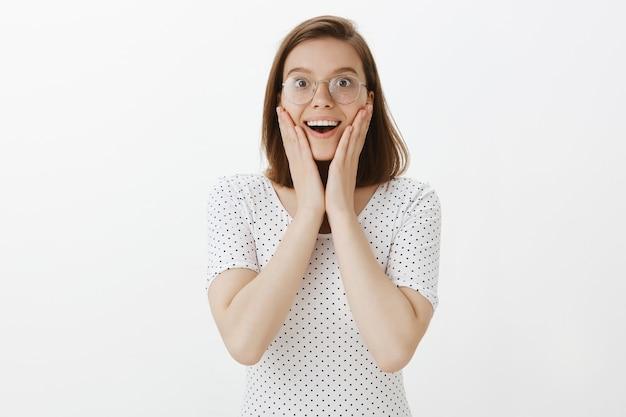 Zdziwiona i rozbawiona kobieta w okularach słuchająca z podnieceniem