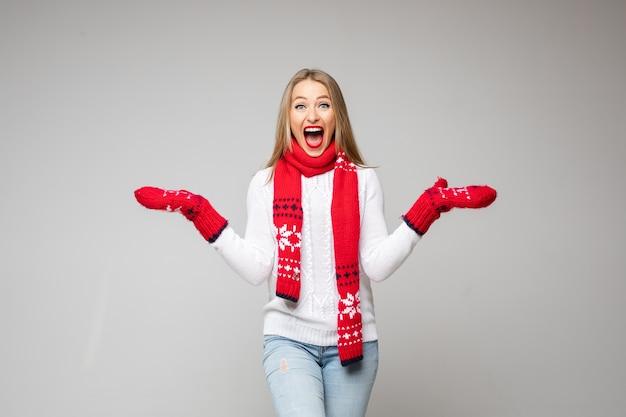 Zdziwiona kaukaska kobieta o blond włosach ubrana w biały sweter, czerwony szalik i rękawiczki z zimowym wzorem. patrząc z otwartymi ustami z podniecenia.