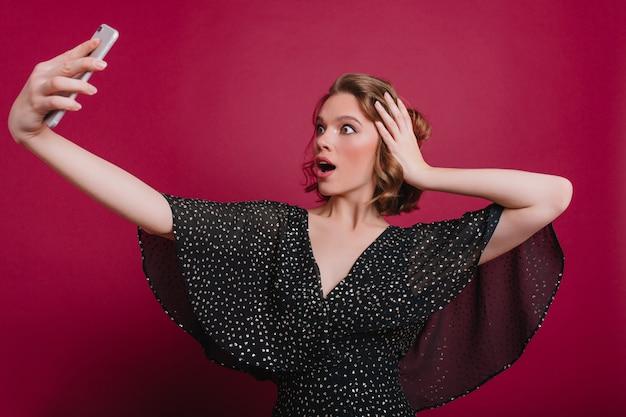 Zdziwiona kobieta bawi się krótkimi lśniącymi włosami podczas robienia selfie. zszokowany kaukaski dziewczyna w vintage casual dress robi sobie zdjęcie za pomocą smartfona.
