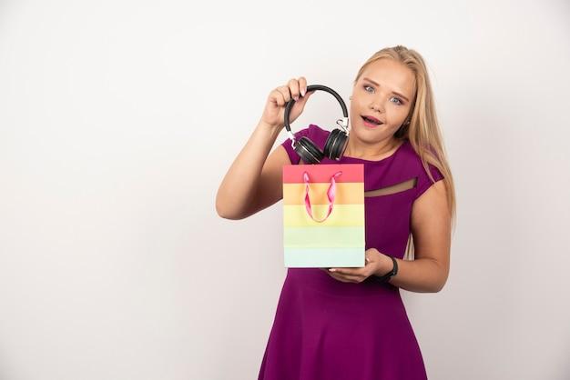Zdziwiona kobieta biorąc słuchawki z torby na prezent.