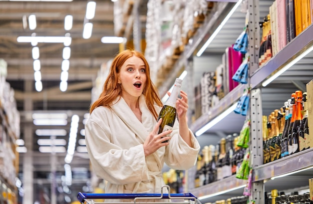 Zdziwiona kobieta cieszy się, że znajduje szampana po obniżonej cenie, stoi z otwartymi ustami, trzymając w rękach butelkę alkoholu, ubrana w szlafrok