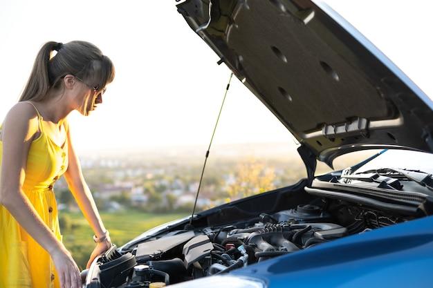 Zdziwiona kobieta-kierowca stojąca obok swojego samochodu z podniesioną maską, sprawdzająca zepsuty silnik.