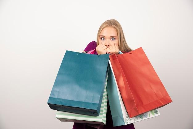 Zdziwiona kobieta niosąca torby na zakupy na białej ścianie.