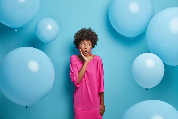 Zdziwiona kobieta o afro włosach, ubrana w odświętną różową sukienkę, z szokiem spogląda w prawo, wstaje
