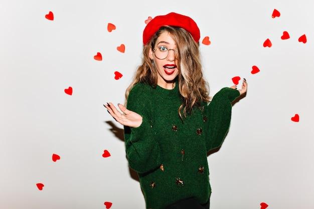Zdziwiona kobieta o jasnobrązowych włosach pozuje na białej ścianie w zielonym swetrze