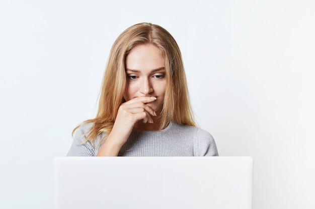 Zdziwiona kobieta o pięknym wyglądzie czyta wiadomości online, skupiając się na laptopie. młody student pracuje przy pracy dyplomowej lub pracy dyplomowej, korzysta z nowoczesnych technologii, na białym