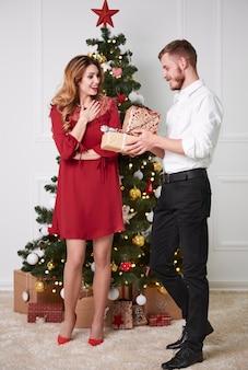 Zdziwiona kobieta odbiera pudełko prezentów