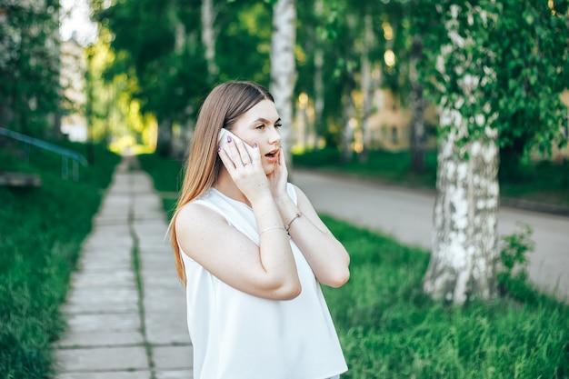Zdziwiona kobieta opowiada na telefonie komórkowym