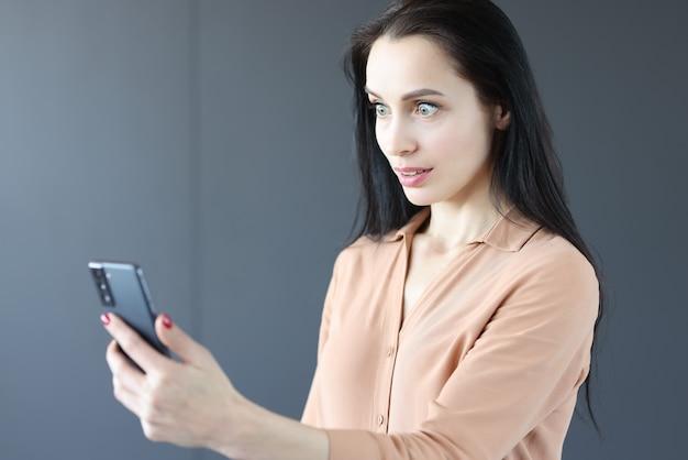 Zdziwiona kobieta patrząc na ekran telefonu komórkowego