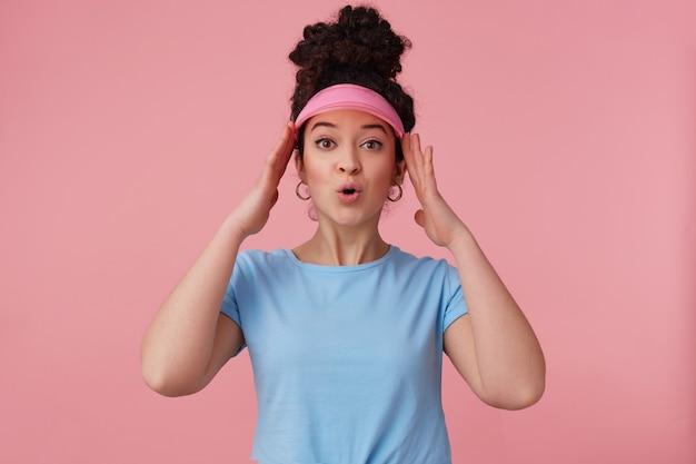Zdziwiona kobieta, piękna dziewczyna z ciemnymi kręconymi włosami w kok. nosi różowy daszek, kolczyki i niebieską koszulkę. uzupełniał. dotykając jej głowy
