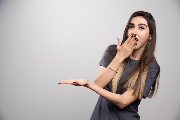 Zdziwiona kobieta pokazując rękę i zakrywając usta.