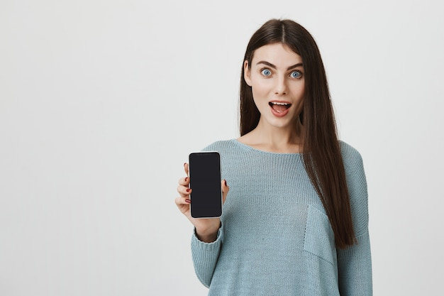 Zdziwiona kobieta pokazująca ekran smartfona zdziwiona