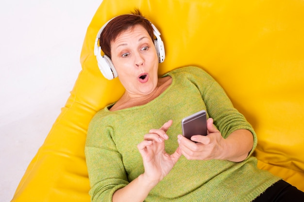 Zdziwiona kobieta słucha muzyki na kanapie
