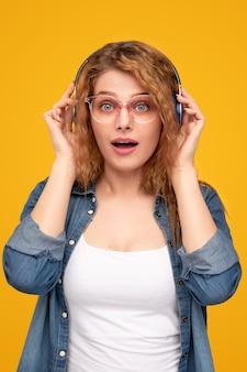 Zdziwiona kobieta słuchająca muzyki