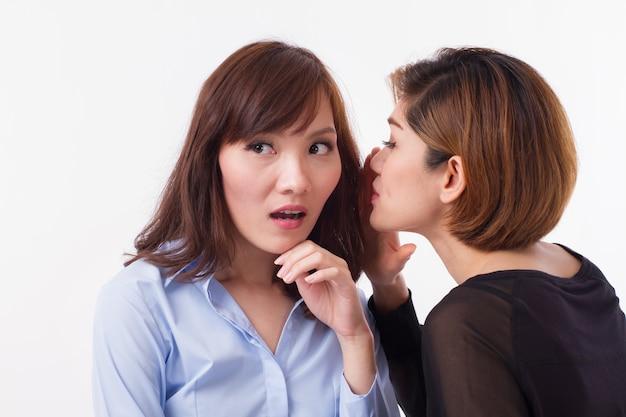 Zdziwiona kobieta słuchająca plotek