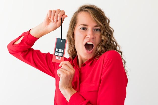 Zdziwiona kobieta trzyma czarną etykietę piątek