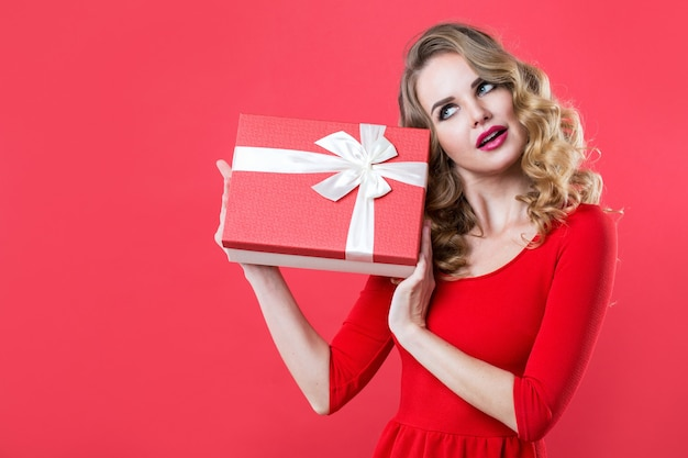 Zdziwiona kobieta trzyma czerwone pudełko w czerwonej sukience. piękna dziewczyna z kręconymi włosami.