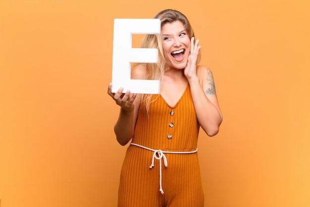 Zdziwiona kobieta trzyma literę e alfabetu, tworząc słowo