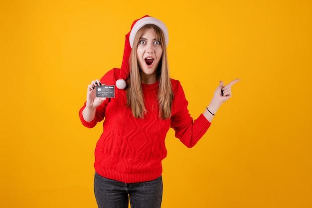 Zdziwiona kobieta trzyma szablon kredytową kartę i wskazuje przy kopii przestrzenią jest ubranym santa kapelusz
