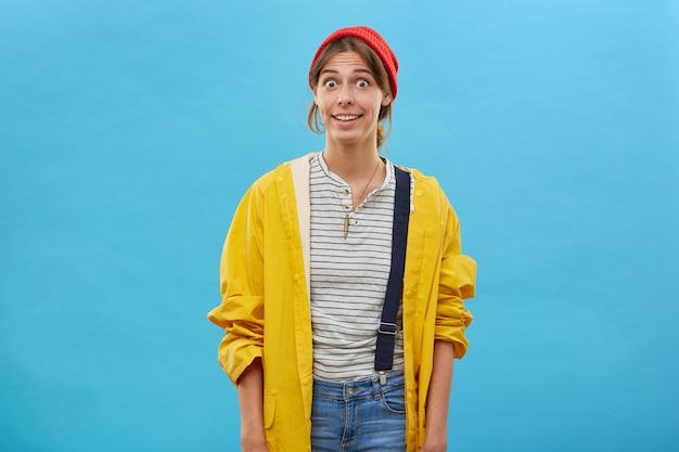 Zdziwiona kobieta ubrana w zwykłe ciuchy pozująca na niebieskiej ścianie, wpatrująca się w zdumione oczy. młoda kobieta w luźnym żółtym płaszczu przeciwdeszczowym i czerwonym kapeluszu z podekscytowanym wyglądem