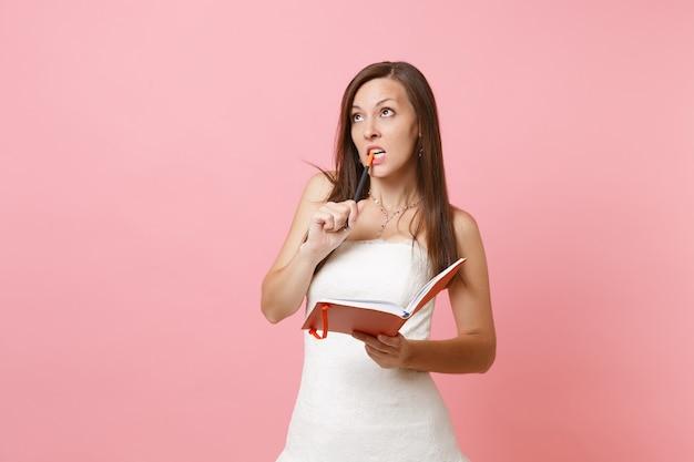 Zdziwiona kobieta w białej sukni, gryząca ołówek, szukając pomysłów, pisząc notatki w pamiętniku, zeszycie