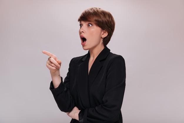Zdziwiona kobieta w czarnym garniturze wskazuje w lewo. atrakcyjna ciemnowłosa dama w klasycznej kurtce wygląda na zszokowaną na odosobnionym tle
