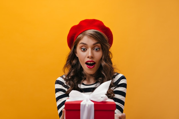 Zdziwiona kobieta w czerwonym berecie dostaje pudełko. kręcone młoda dziewczyna z jasną szminką w kapeluszu, pozowanie na na białym tle.
