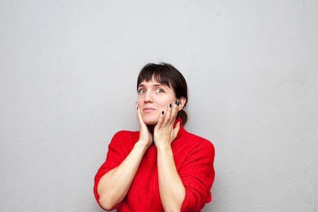 Zdziwiona kobieta w czerwonym swetrze na szarej ścianie