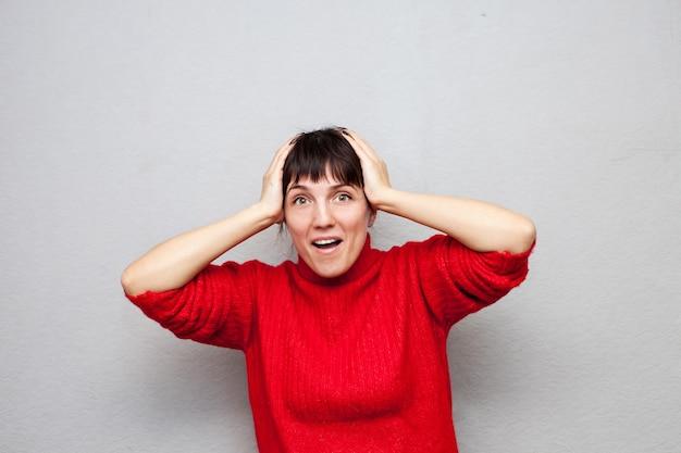 Zdziwiona kobieta w czerwonym swetrze, trzymając głowę rękami