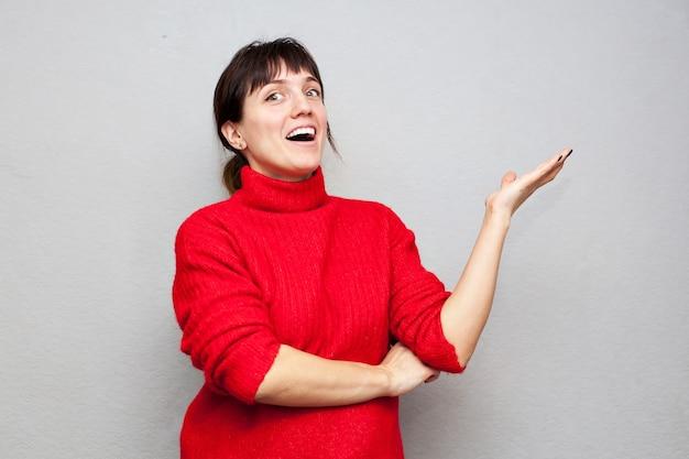 Zdziwiona kobieta w czerwonym swetrze wskazuje bokiem na szarej ścianie