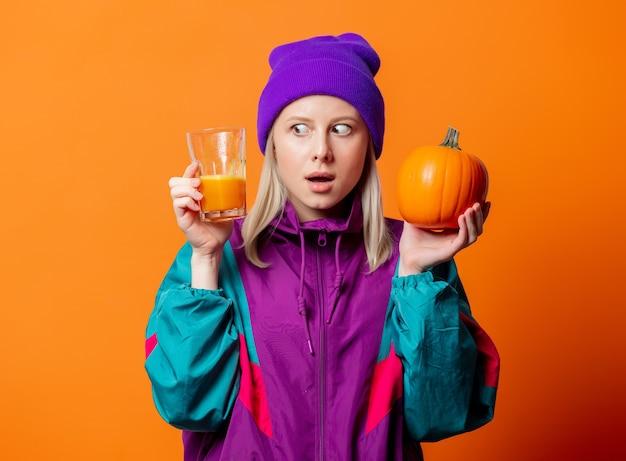 Zdziwiona kobieta w dresie z lat 90. z sokiem dyniowym na pomarańczowo