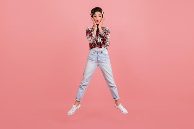 Zdziwiona kobieta w dżinsach skoki na różowym tle. ładna dziewczyna pinup w kraciastej koszuli wyrażająca zdziwione emocje.