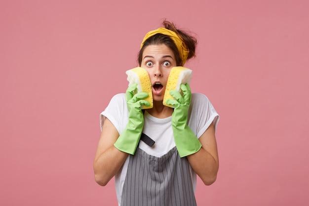 Zdziwiona kobieta w fartuchu i zwykłym ubraniu, ubrana w zielone gumowe rękawiczki, trzymająca dwie schludne gąbki na policzkach, zdając sobie sprawę, że powinna wykonać dużo pracy. zdumiona kobieta zamierza wykonać swoje prace domowe