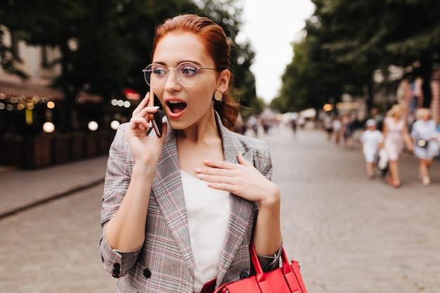 Zdziwiona kobieta w okularach patrzy w kamerę
