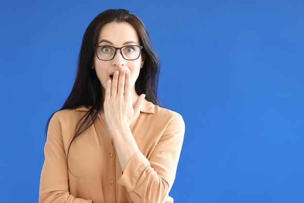 Zdziwiona kobieta w okularach zakrywa usta dłonią