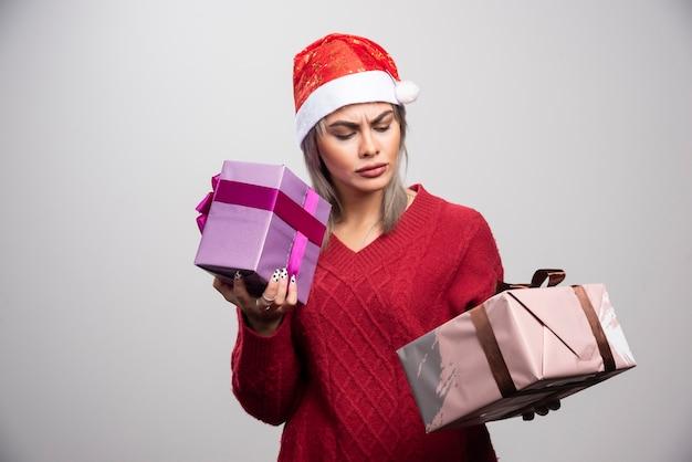 Zdziwiona kobieta w santa kapeluszu patrząc na prezenty bożonarodzeniowe.