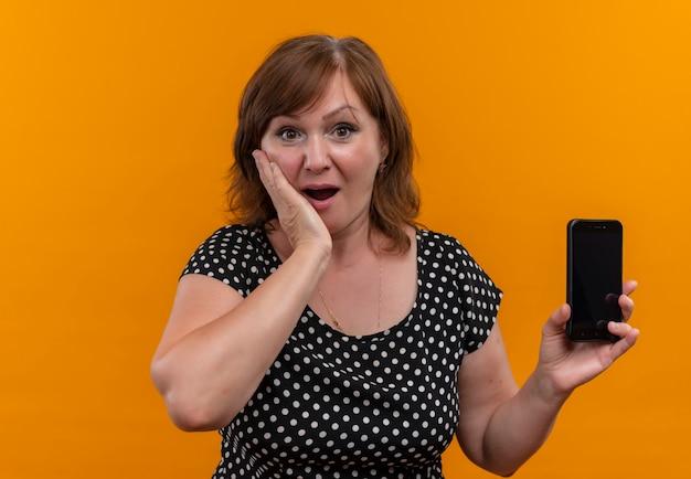 Zdziwiona kobieta w średnim wieku, trzymając telefon komórkowy i kładąc rękę na policzku na pomarańczowej ścianie z miejsca na kopię